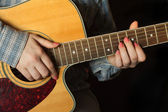 Girl  playing an acoustic guitar closeup — Стоковое фото