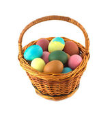Color Easter eggs in brown basket isolated — Stock Photo