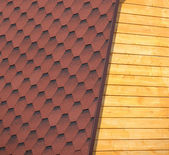 Wooden house wall and part of red roof from soft tile closeup — Stock Photo