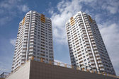 Two residential buildings in a city over blue sky with clouds closeup — Stock Photo