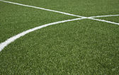 Part of a soccer field with green synthetic grass and white lines — Stock Photo
