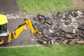 Wegenbouwmachine breekt oude asfaltweg — Stockfoto