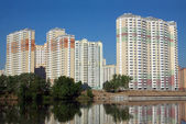 New buildings over river and clear blue sky in summer day — Stock Photo