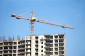 Içamento de guindaste de torre e topo de prédio de construção — Fotografia Stock