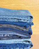 Colored jeans on cupboard shelf, front view close-up — Stock Photo