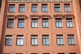 Front view of brick wall contemporary apartment building with windows — Stock Photo