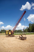 Excavator standing on sand near forest on summer day — Stock Photo