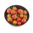 Many ripe tomatoes in purple bowl closeup isolated — Stock Photo #51384951
