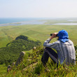 Man looking in binoculars, the border of Russia with North Korea — Stock Photo #24626073