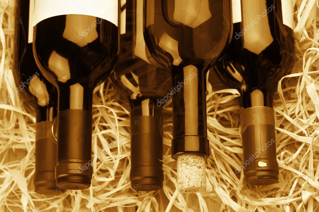 Stack of various wine bottles lying on straw. Monochrome toned image. — Foto Stock #12022416