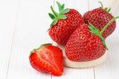 Strawberries on white wood — Stock Photo