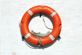 Red Life Buoy hanging on the wall — Stock Photo