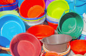 Many plastic basins in different colors, as a stack on a open ma — Stock Photo