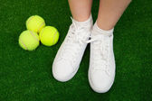 Tennis sneakers on green — Stok fotoğraf