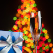 Stock Photo: Champagne and gift against bokeh lights