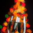 Stock Photo: Champagne glasses against christmas tree bokeh lights