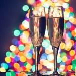 Champagne glasses against christmas tree bokeh lights — Stock Photo #16878341