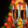 Champagne glasses against christmas tree bokeh lights — Stock Photo