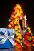 Champagne and gift against bokeh lights — Stock Photo