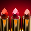 Three lipsticks on red background — Stock Photo