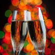 Champagne glasses against christmas tree bokeh lights — Stock Photo #17397019
