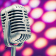 Foto de Stock  : Retro microphone on purple disco background