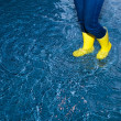 Rubber boots walking in the water — Stock Photo