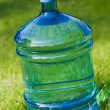 Water big bottle on green lawn background — Stock Photo