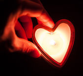 Hand holding burning candle heart — Stock Photo