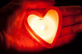 Burning candle heart on hand — Stock Photo