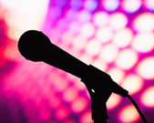 Silhouette of microphone against purple disco background — Stock Photo