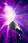 Microphone against violet disco background — Stock Photo