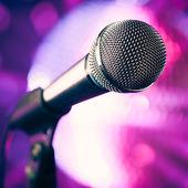 Mikrofonen mot lila disco bakgrund — Stockfoto