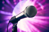 Microphone against purple disco background — Stock Photo