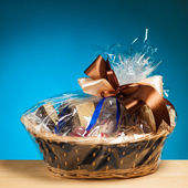 Gift in a basket against blue background — Stockfoto