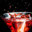 Stock Photo: Red splashing cocktail on black