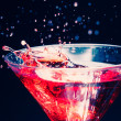 Red splashing cocktail on black — Stock Photo