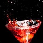 Red splashing cocktail on black — Stock Photo #22493913