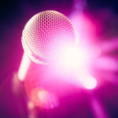 Microphone on stage with purple shiny glare — Stock Photo