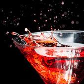 Röda stänk cocktail på svart — Stockfoto