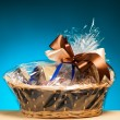 Gift in a basket against blue background — Stock Photo #23133938