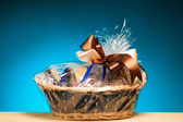 Gift in a basket against blue background — Stock Photo
