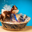 Gift in a basket against blue background — Stock Photo #23982973