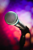 Microphone against purple background — Stock Photo