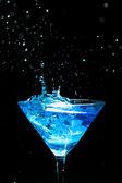 Blue splashing cocktail on black — Stock Photo