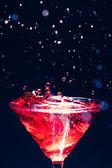 Red splashing cocktail on black — Stock Photo