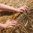 Hands pushing on hay bale — Stock Photo