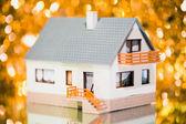 Festive house against golden bokeh background — Stock Photo