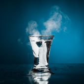 Shot glass of vodka with ice vapor — Stock Photo