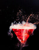 Red cocktail with splash and ice vapor — Stock Photo